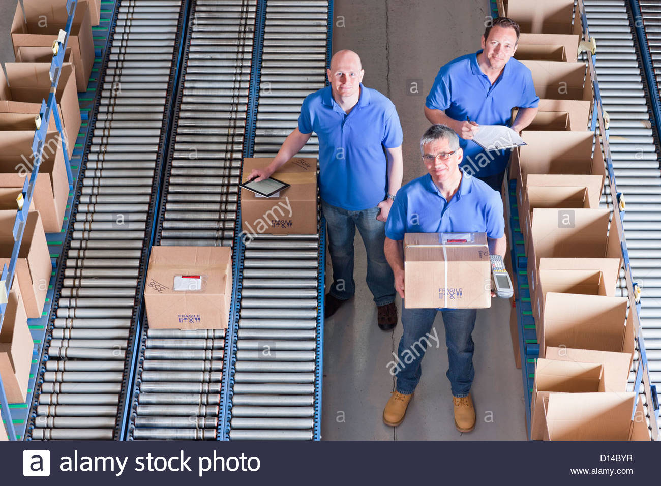 Portrait of smiling workers packing boxes on conveyor belts in distribution warehouse Stock Photo