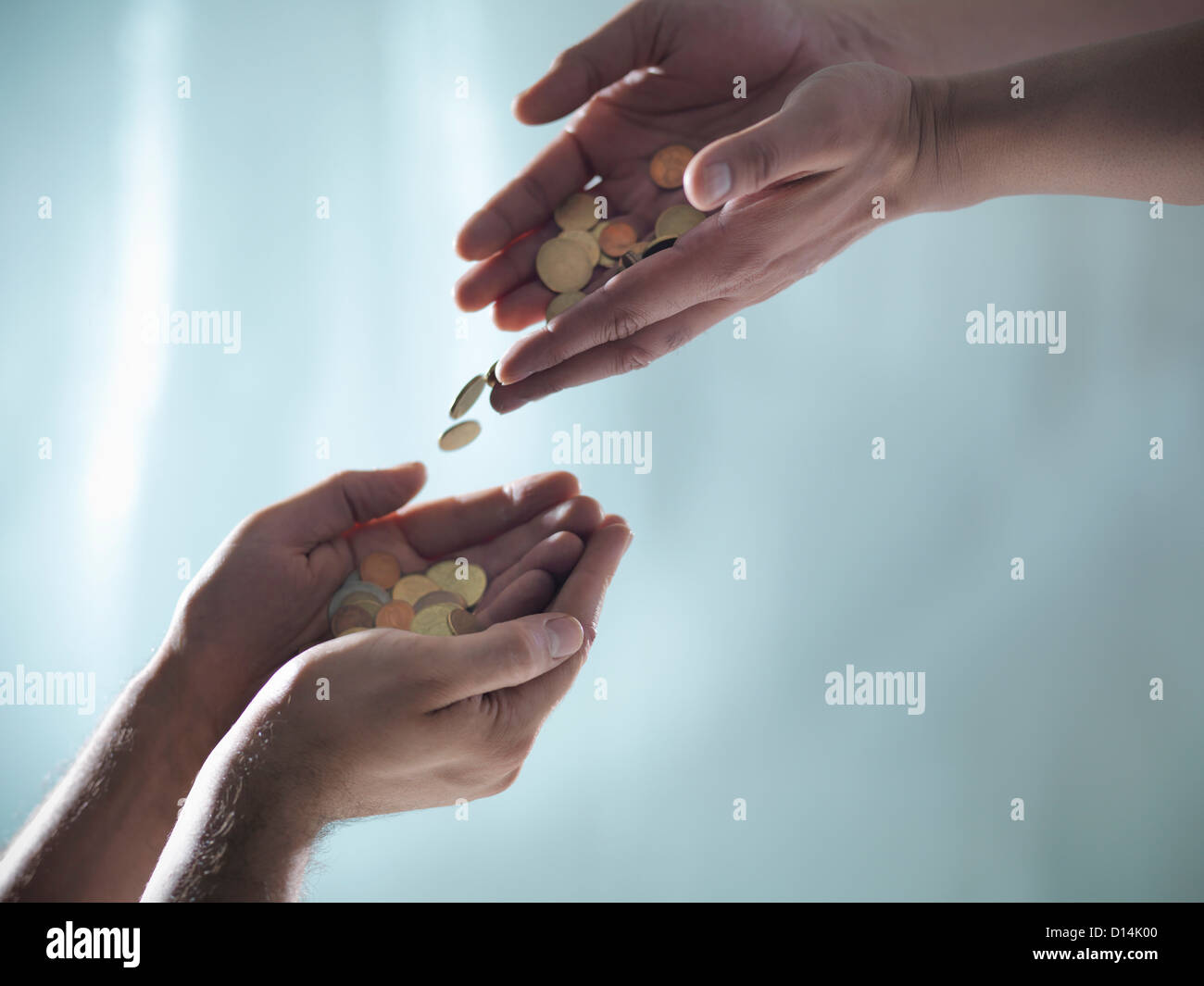 Hands passing pile of coins - Stock Image