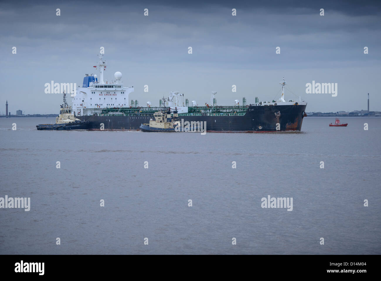 Tugboats pushing ship to harbor - Stock Image