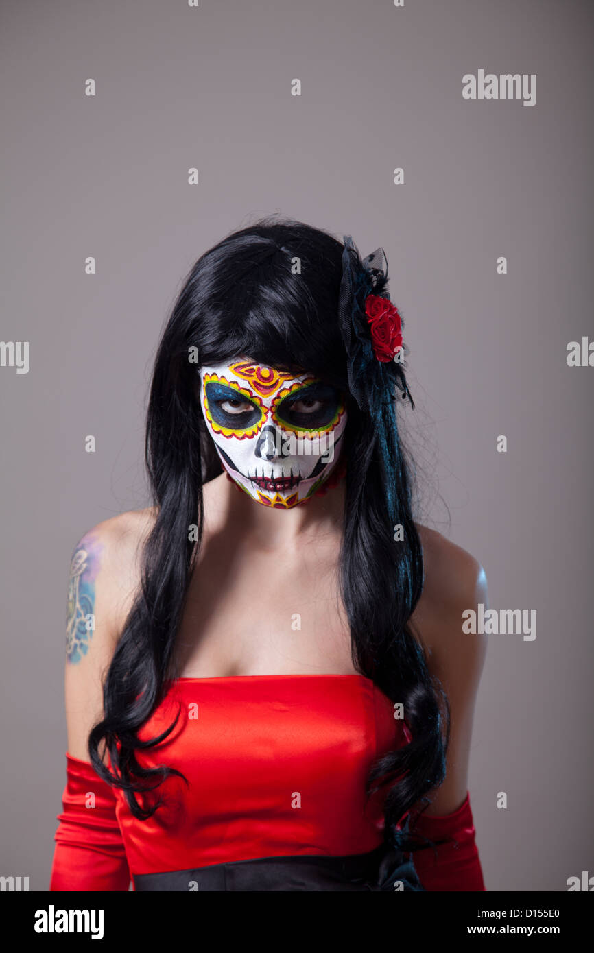 young woman with sugar skull halloween make up wearing red dress the day of the dead
