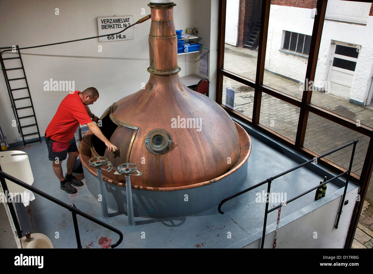 Brewer inspecting brass boil kettle in the Watou brewery near Poperinge, West Flanders, Belgium - Stock Image