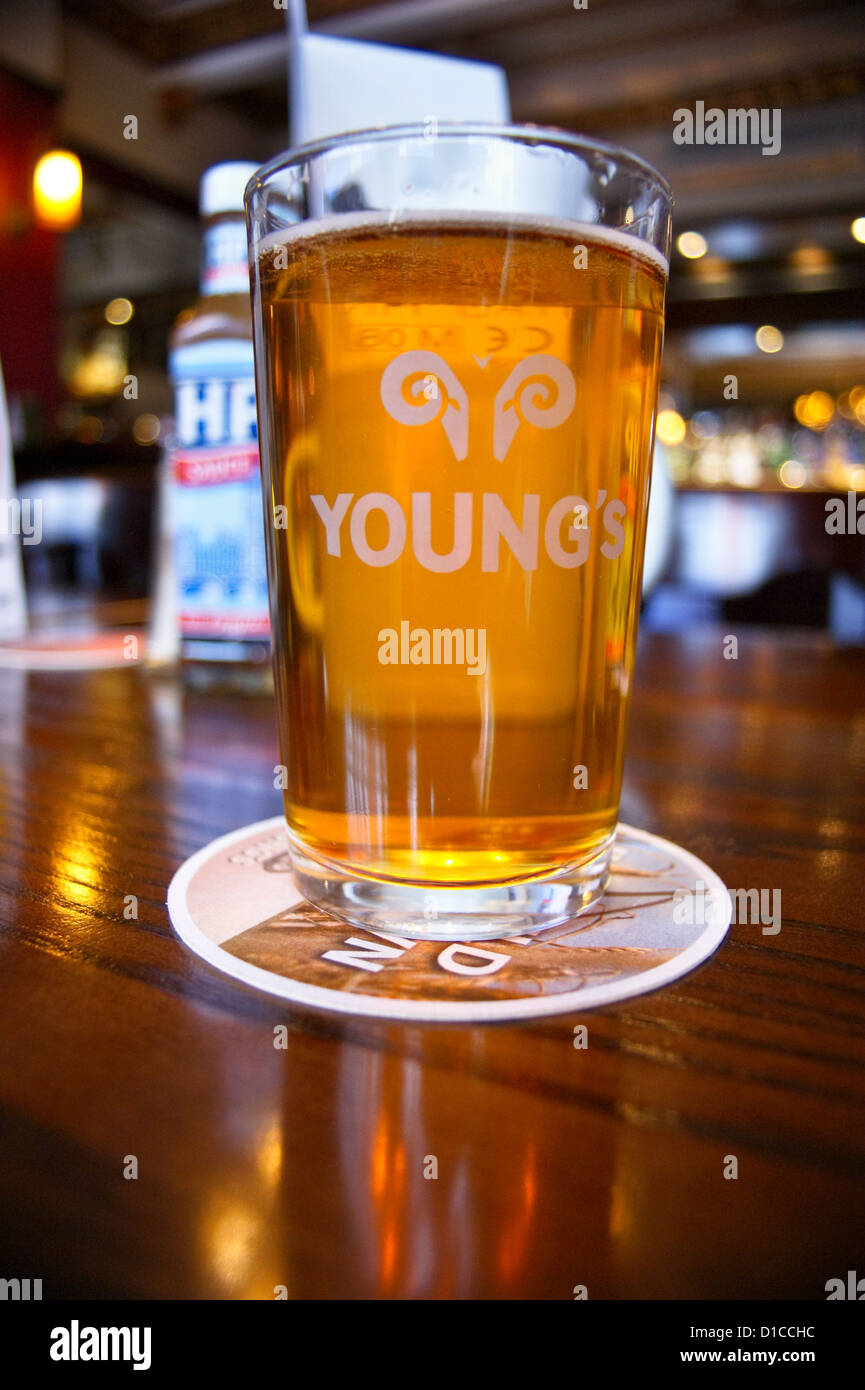 a-pint-of-youngs-ordinary-bitter-ale-with-a-bottle-of-hp-sauce-on-D1CCHC.jpg