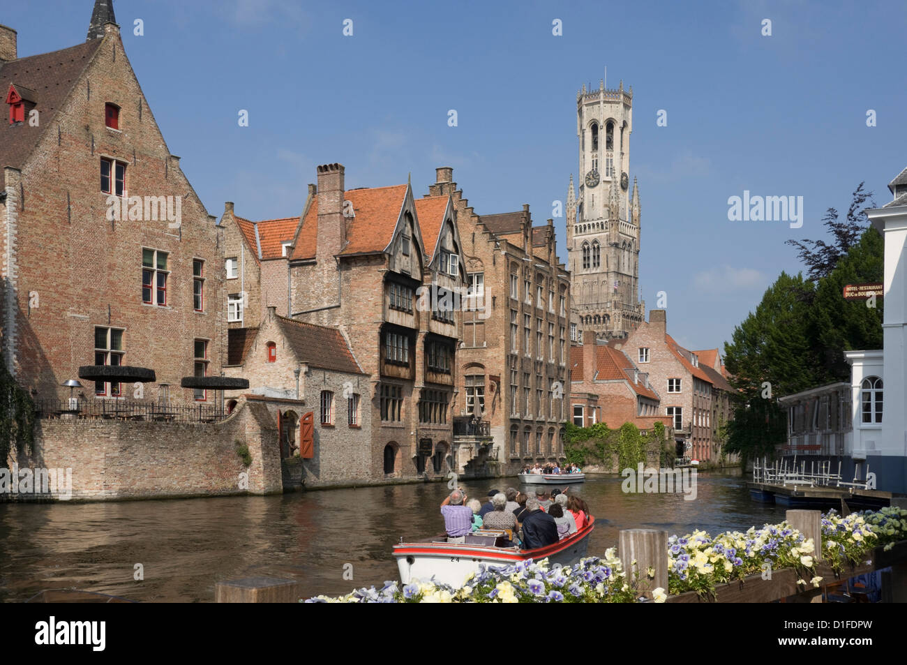 Canal view with a tour launch, Flemish gables and the Belfry tower, Brugge, UNESCO World Heritage Site, Belgium, - Stock Image