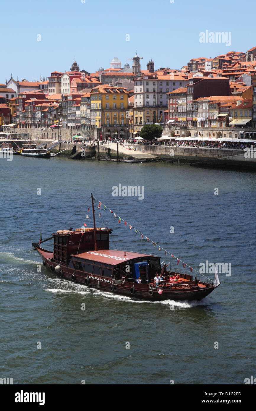 A traditional Rabelo boat, once used for shipping wine grapes, cruises on the River Douro, Porto, Douro, Portugal, - Stock Image