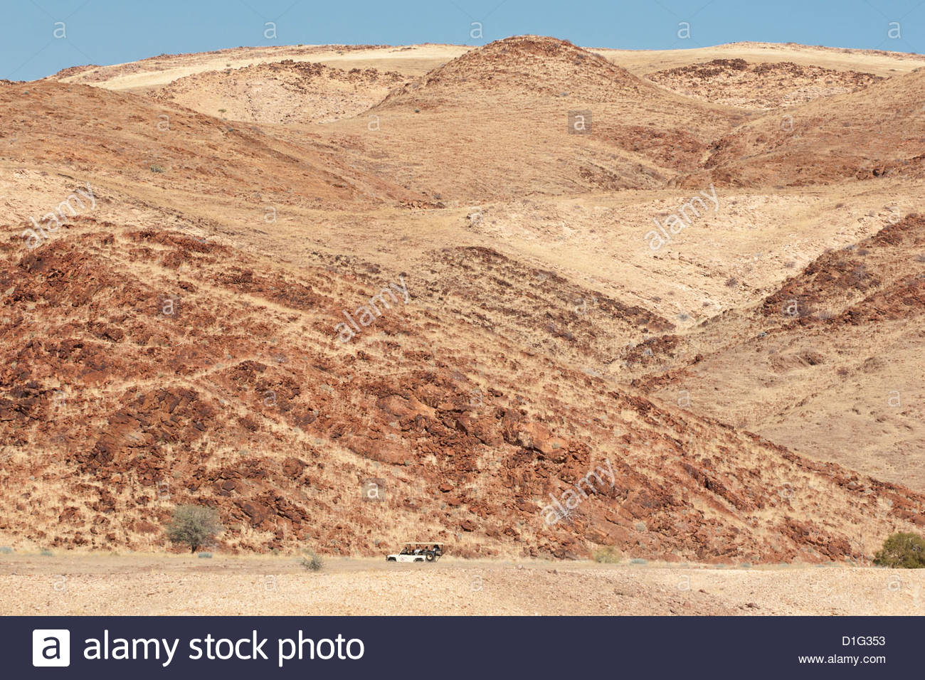 Red rocky landscape with jeep in distance, Purros Conservancy Wilderness, Kaokoland, Namibia, Africa - Stock Image