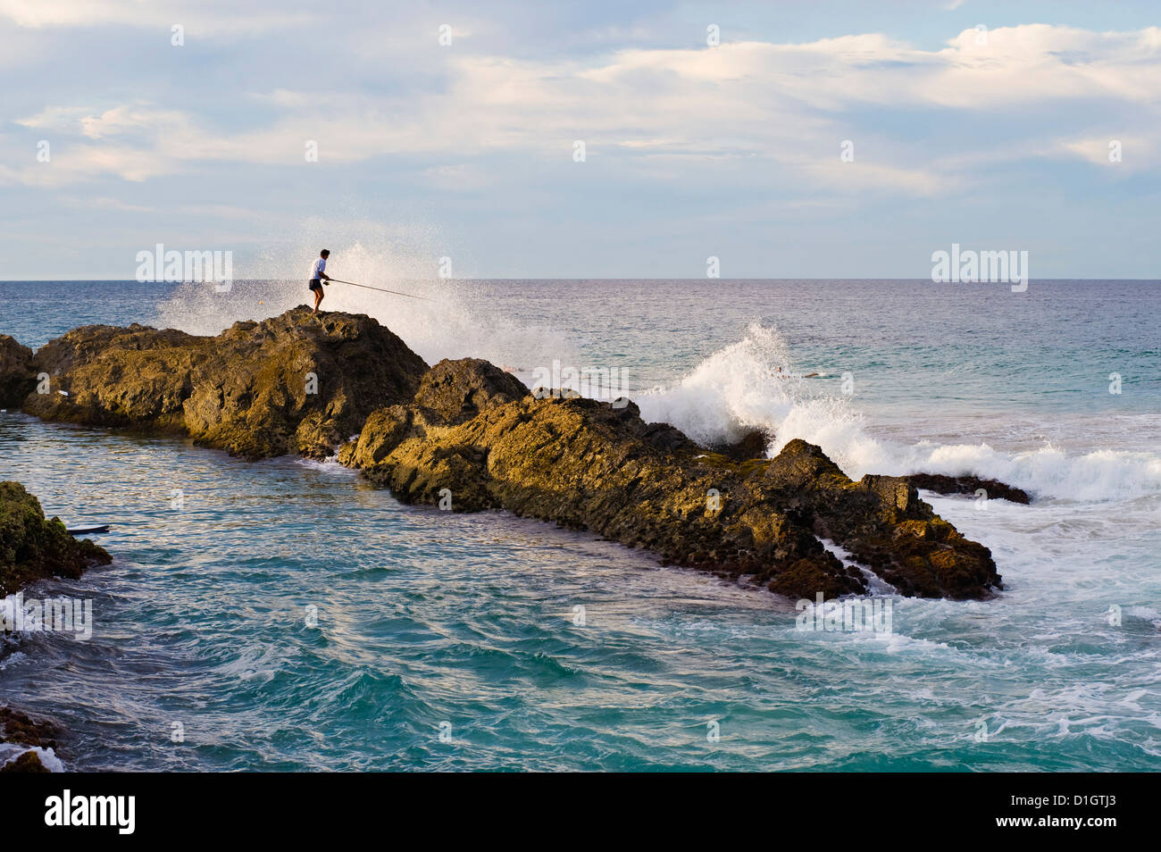 Fisherman getting hit by a wave while rock fishing at Snapper Rocks, Tweed Heads, Gold Coast, Queensland, Australia, - Stock Image