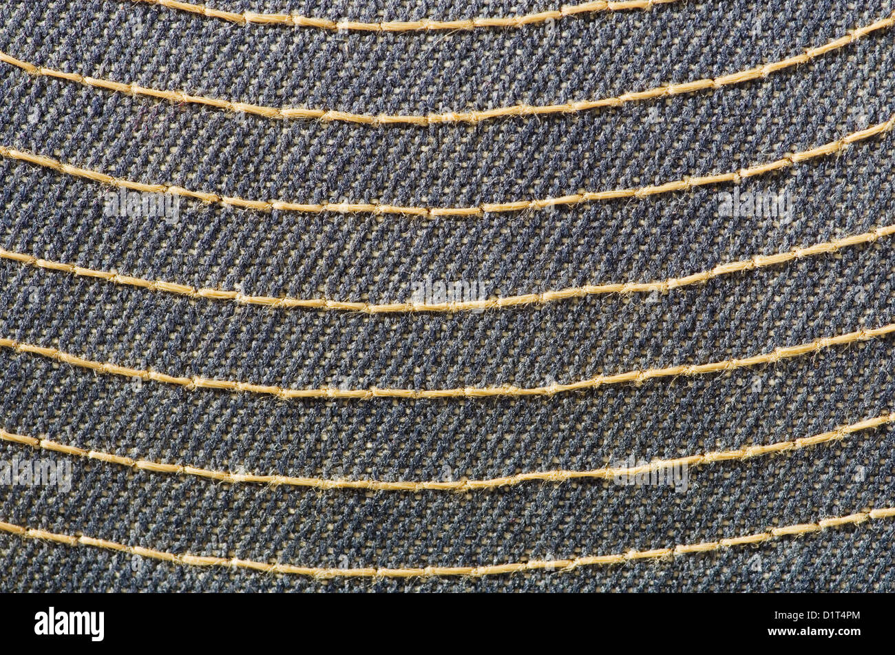 blue cloth with yellow stitching macro background texture - Stock Image