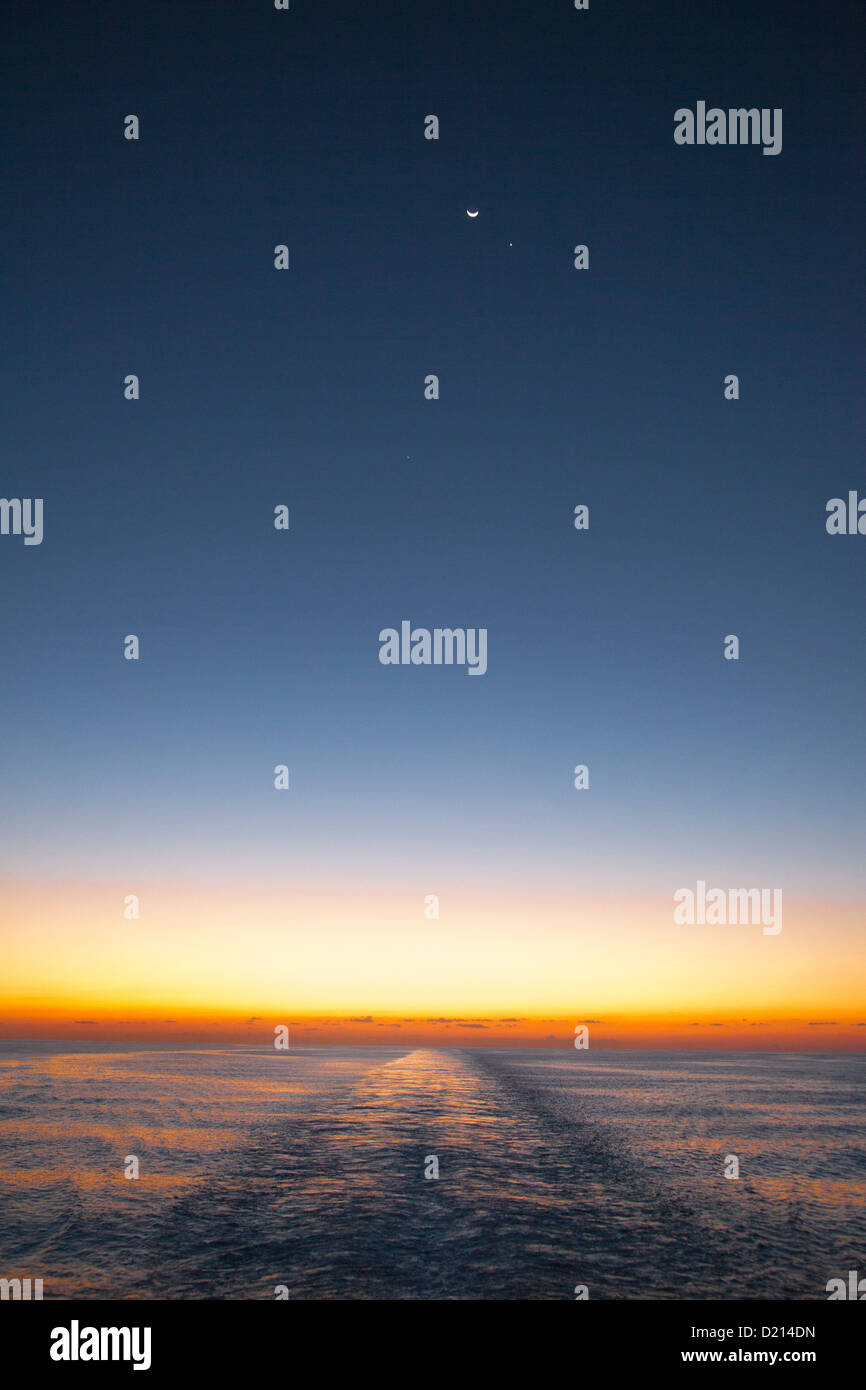 Horizon at dusk with moon, planets and wake from the cruise ship MS Deutschland (Reederei Peter Deilmann), Caribbean - Stock Image