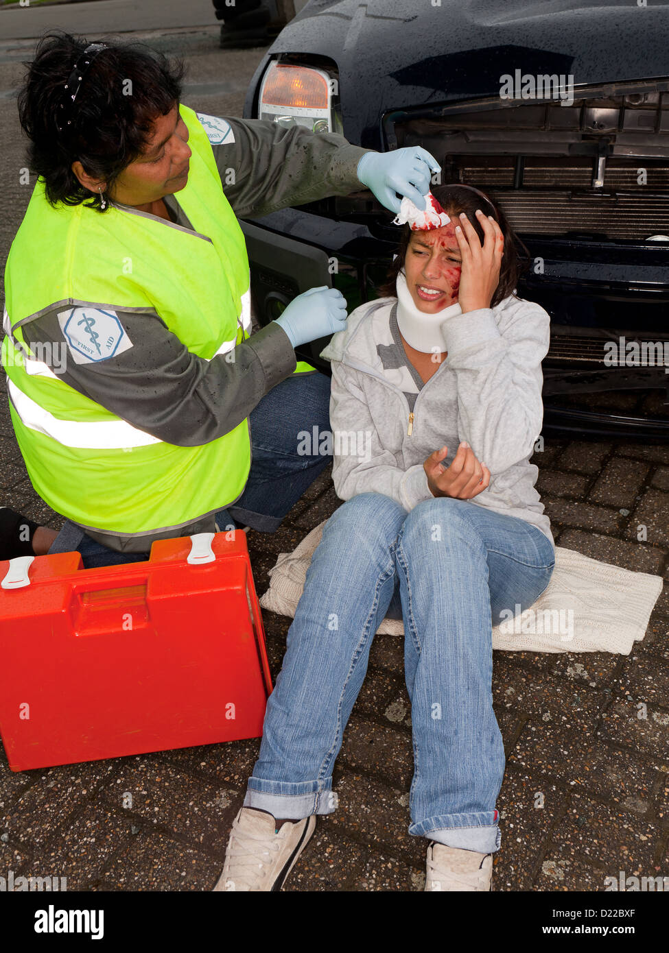 Female paramedic attending to a young car crash victim (the sleeve badges have been replaced by a non existing logo) - Stock Image