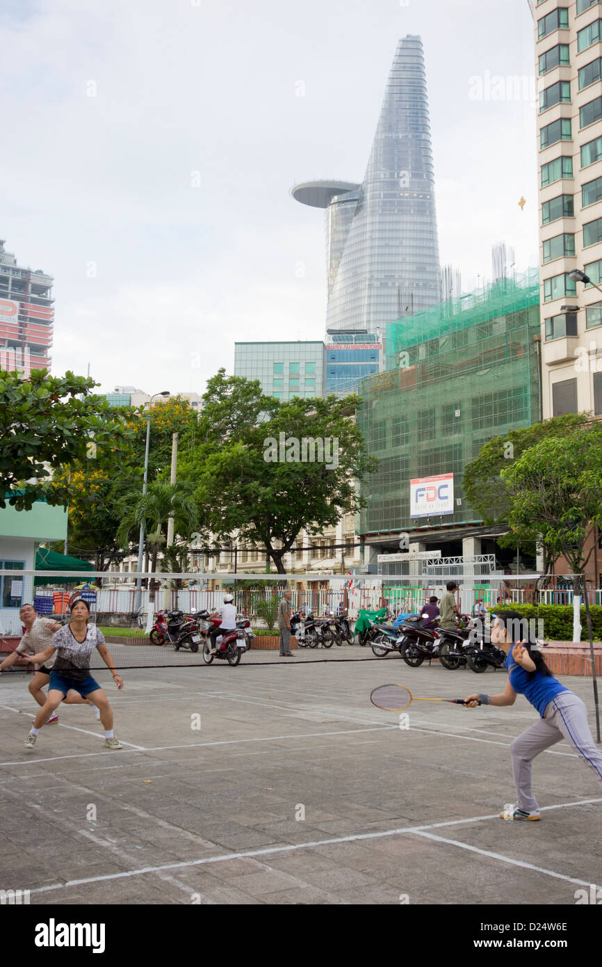 early morning badminton with Bitexco Tower on riverfront court in downtown Ho Chi Minh City; Vietnam - Stock Image