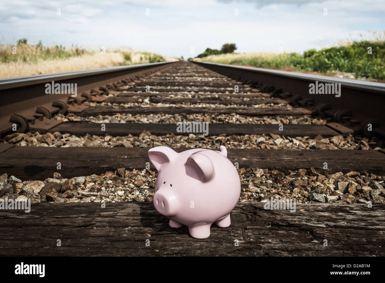 Piggy bank on railroad tracks - Stock Image
