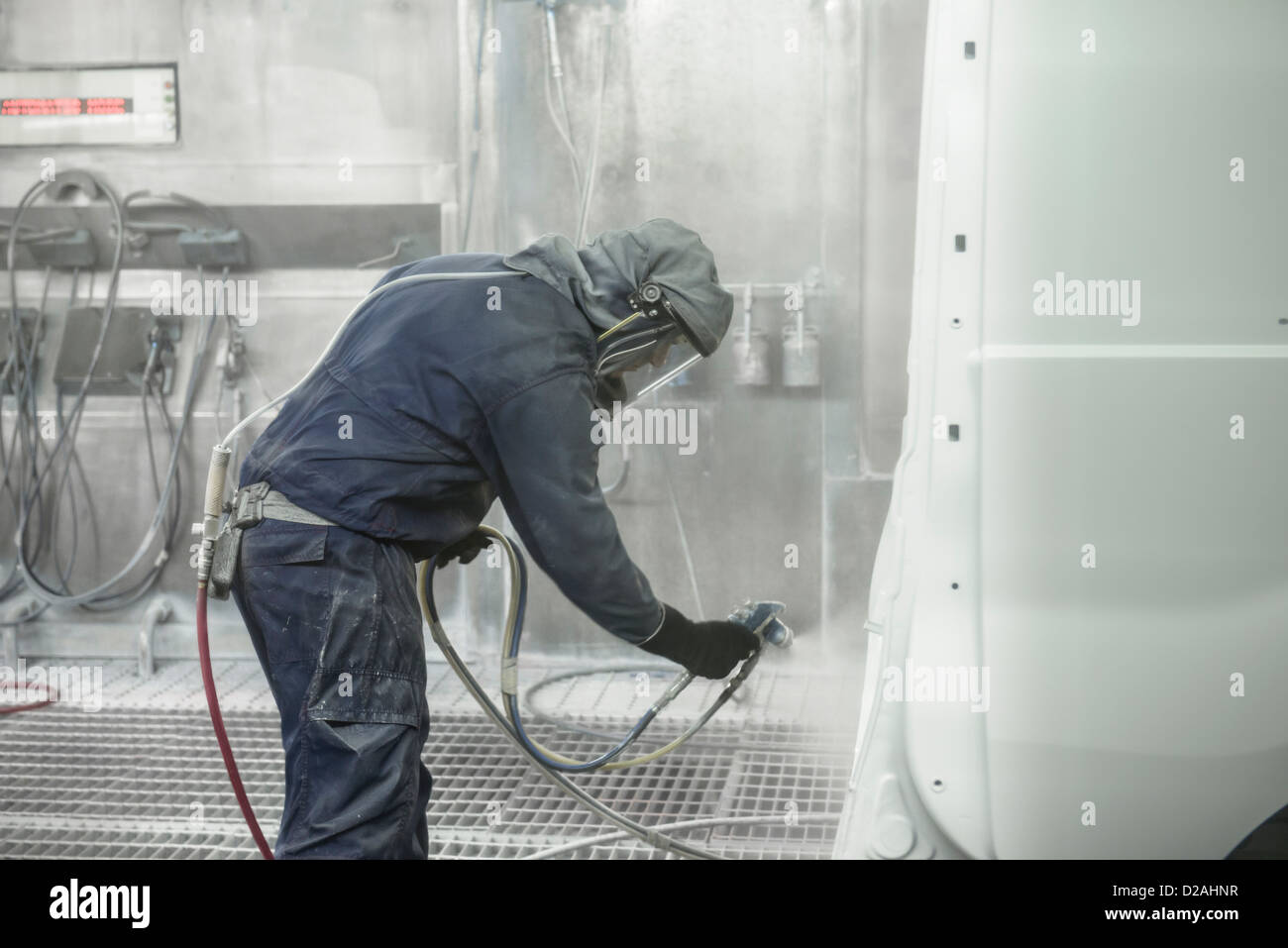 Worker spray painting in car factory - Stock Image