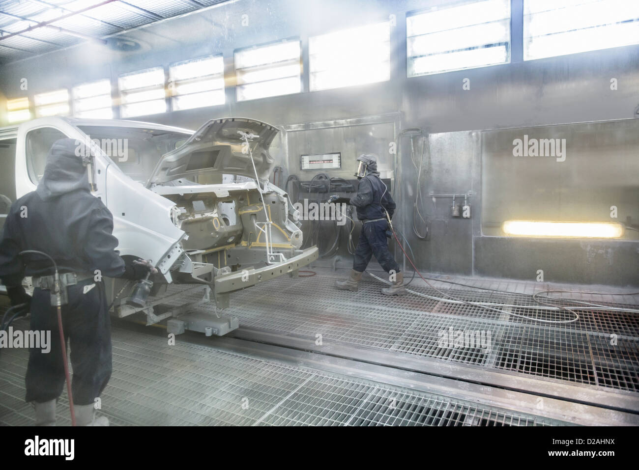 Workers spray painting in car factory - Stock Image