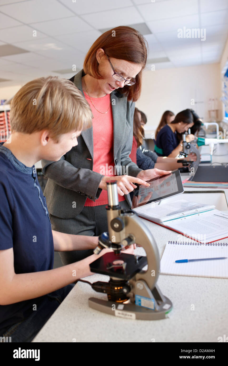 Teacher with student in science class - Stock Image