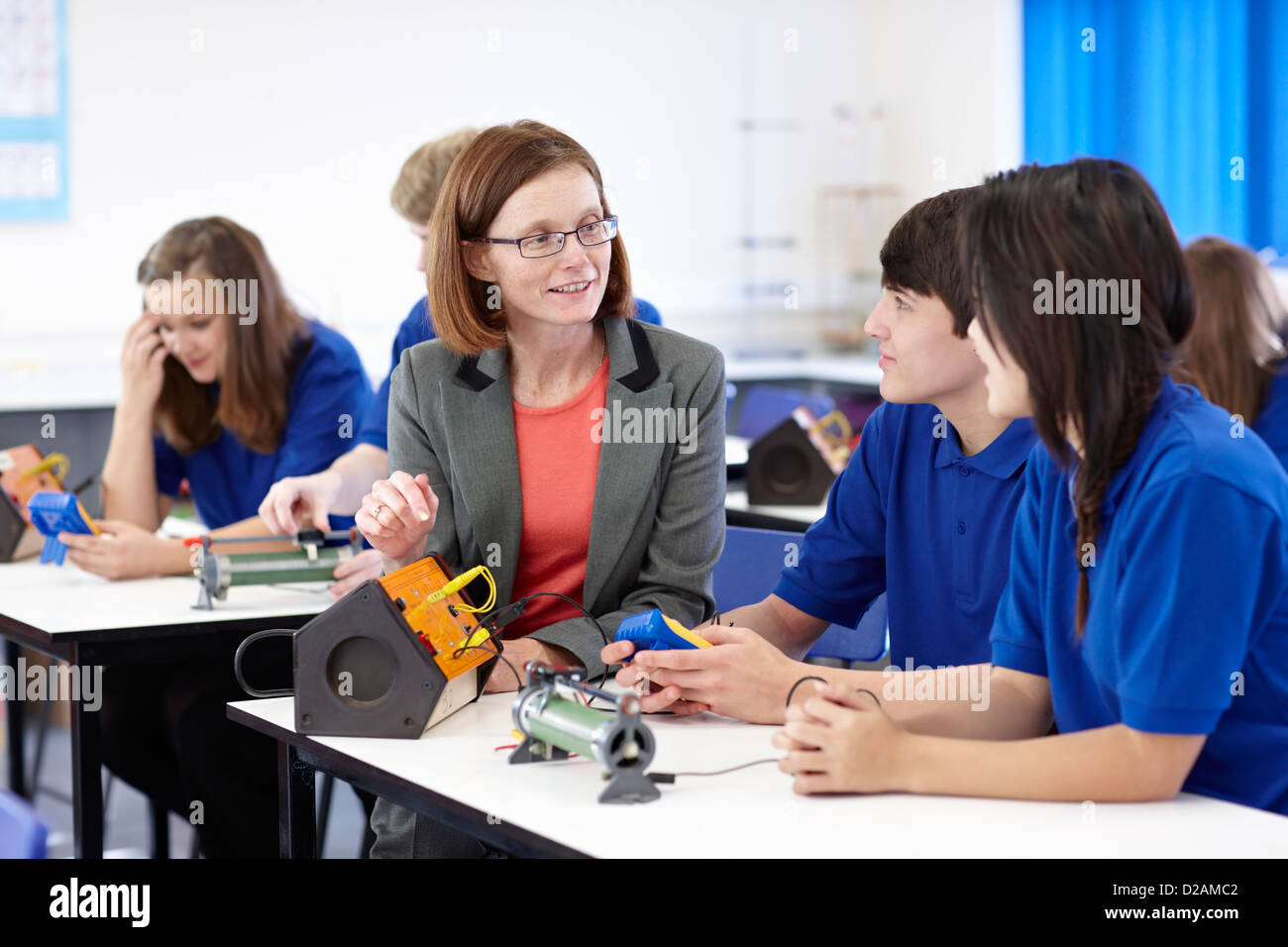 Teacher with students in science class - Stock Image