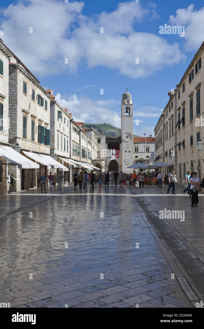 Foot worn glossy roadway in the main street dominated by the clock tower. medieval city of Dubrovnik, Croatia - Stock Image