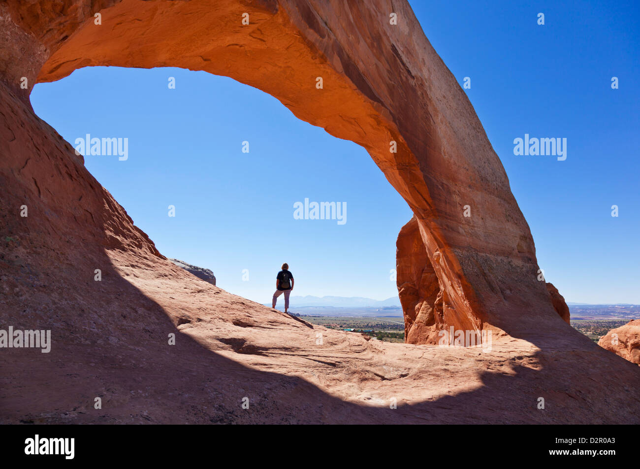 Lone tourist hiker at Wilson Arch, near Moab, Utah, United States of America, North America - Stock Image