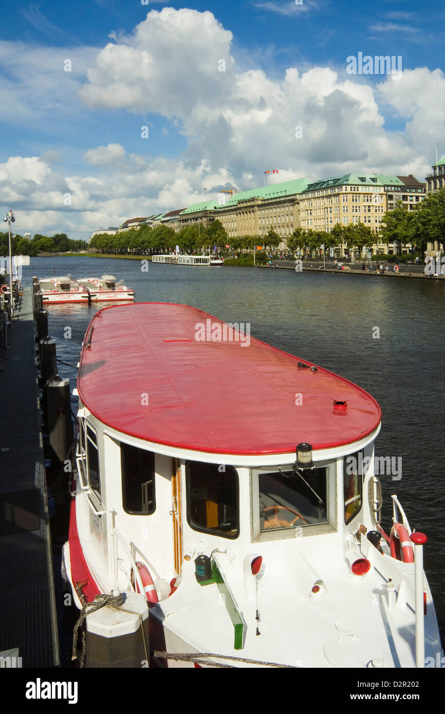 One of the tour boats that ply the Alster Lake, moored at the Jungfernstieg with the Ballindamm beyond, Hamburg, - Stock Image