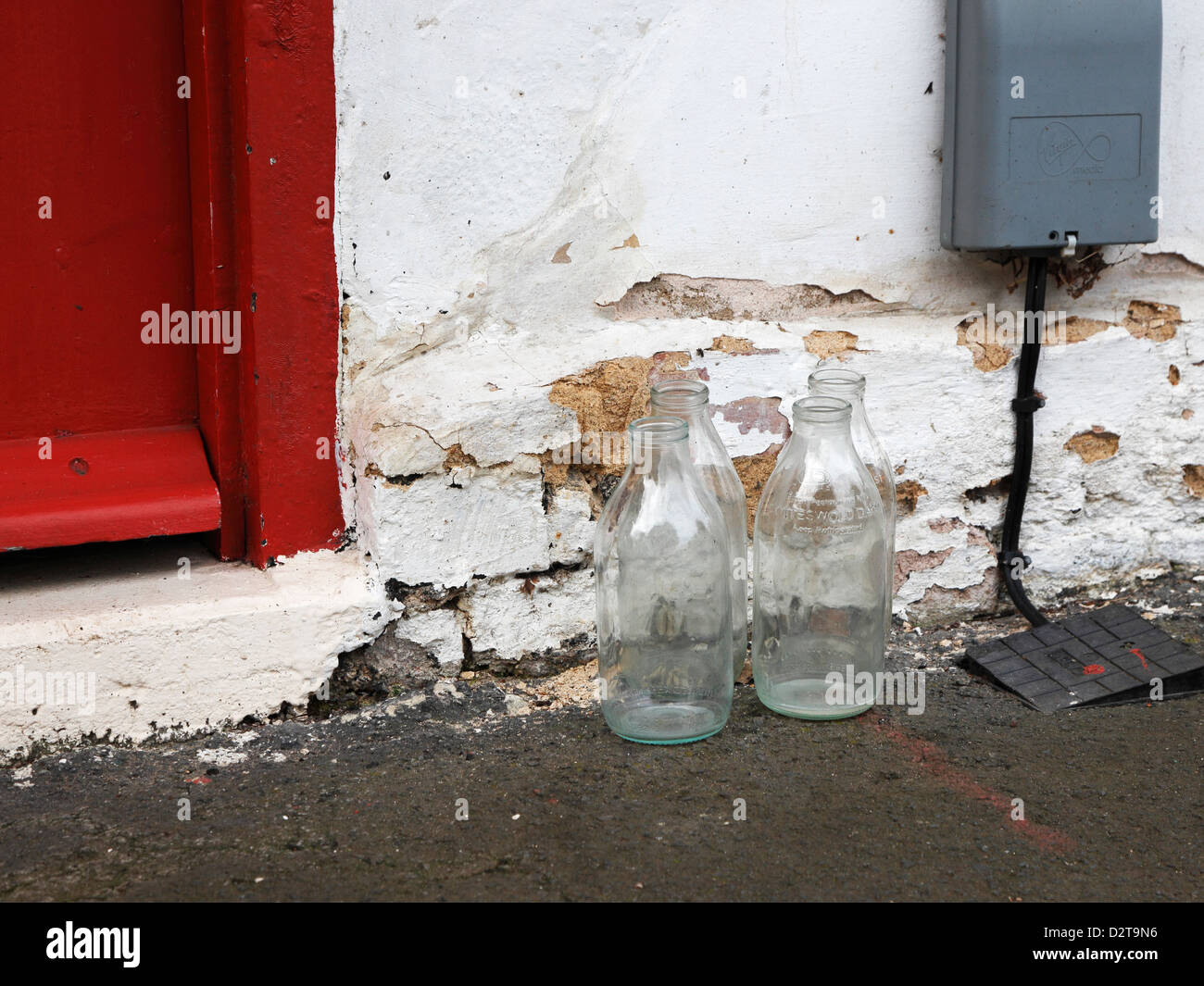 Empty milk bottles at doorstep awaiting collection Milton Cambridgeshire Stock Photo
