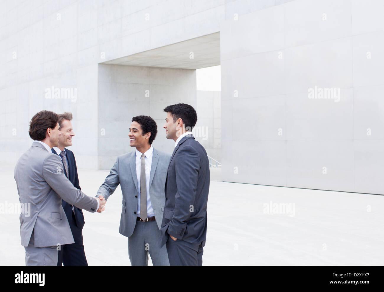 Smiling businessmen shaking hands outside cultural center - Stock Image