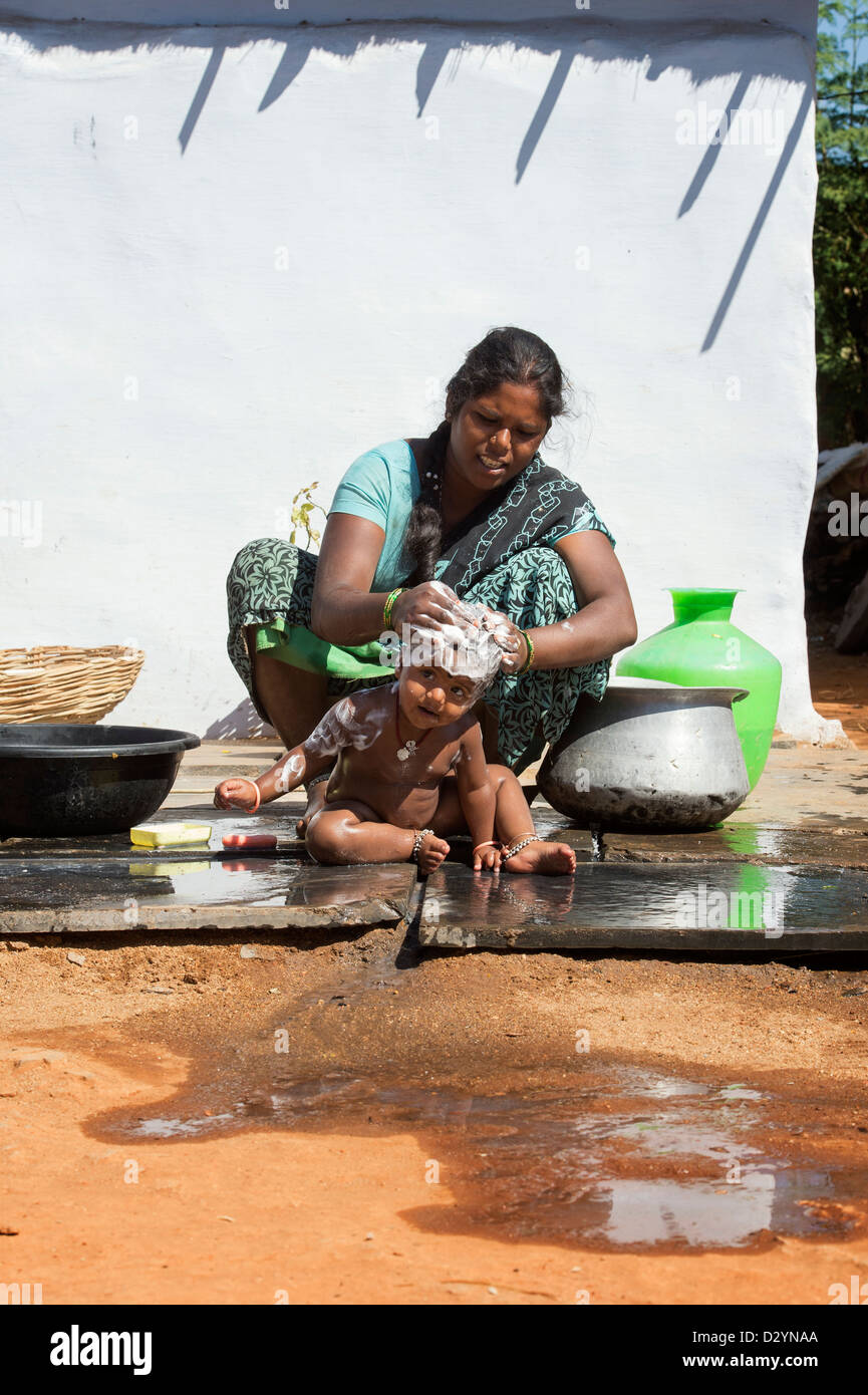 Indian village baby being washed by his mother. Andhra Pradesh, India - Stock Image