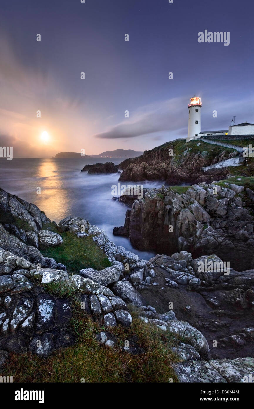 Fanad Head captured as a full moon rises behind the Lighthouse. - Stock Image