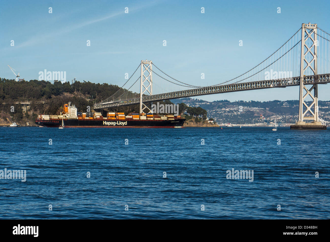 Container cargo ship passing under the Bay Bridge in San Francisco California - Stock Image
