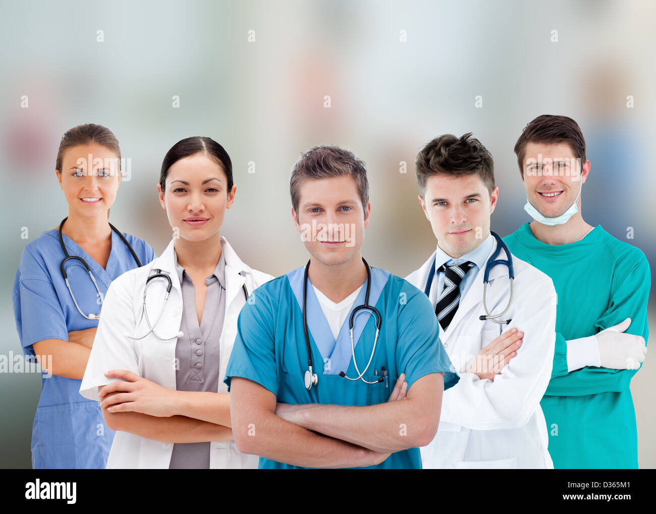 Smiling hospital workers standing in line - Stock Image