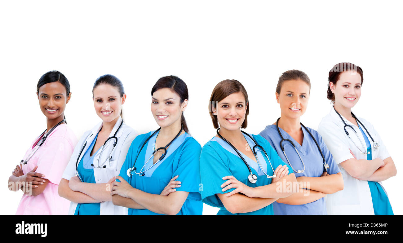 Smiling female hospital workers standing arms folded in line - Stock Image