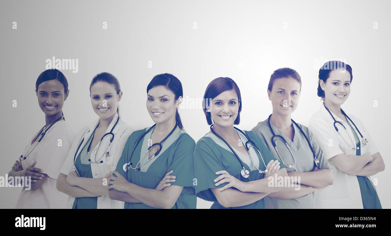 Female hospital workers standing arms folded in line - Stock Image