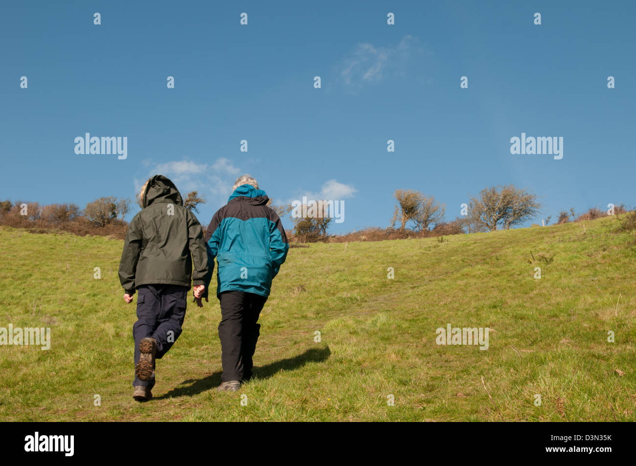 Two ramblers in walking jackets, boots and trousers energetically walking up a steep hill on a sunny spring day - Stock Image