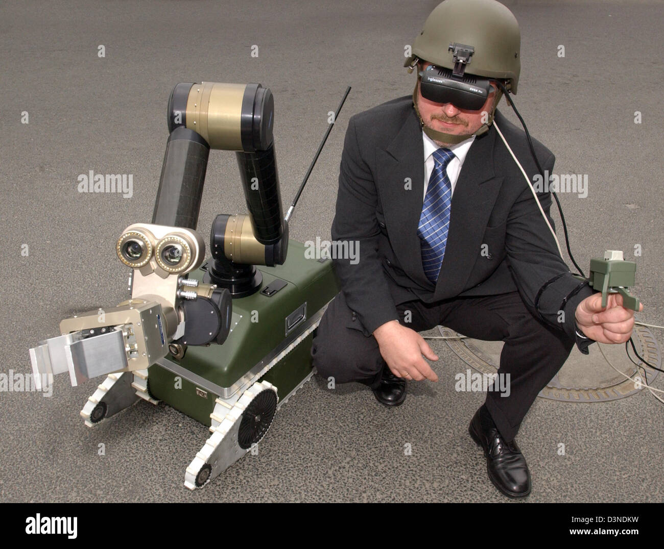An employee of robotics manufacturer 'Robowatch und Diehl BGT Defense ABC' operates a modular robot for - Stock Image