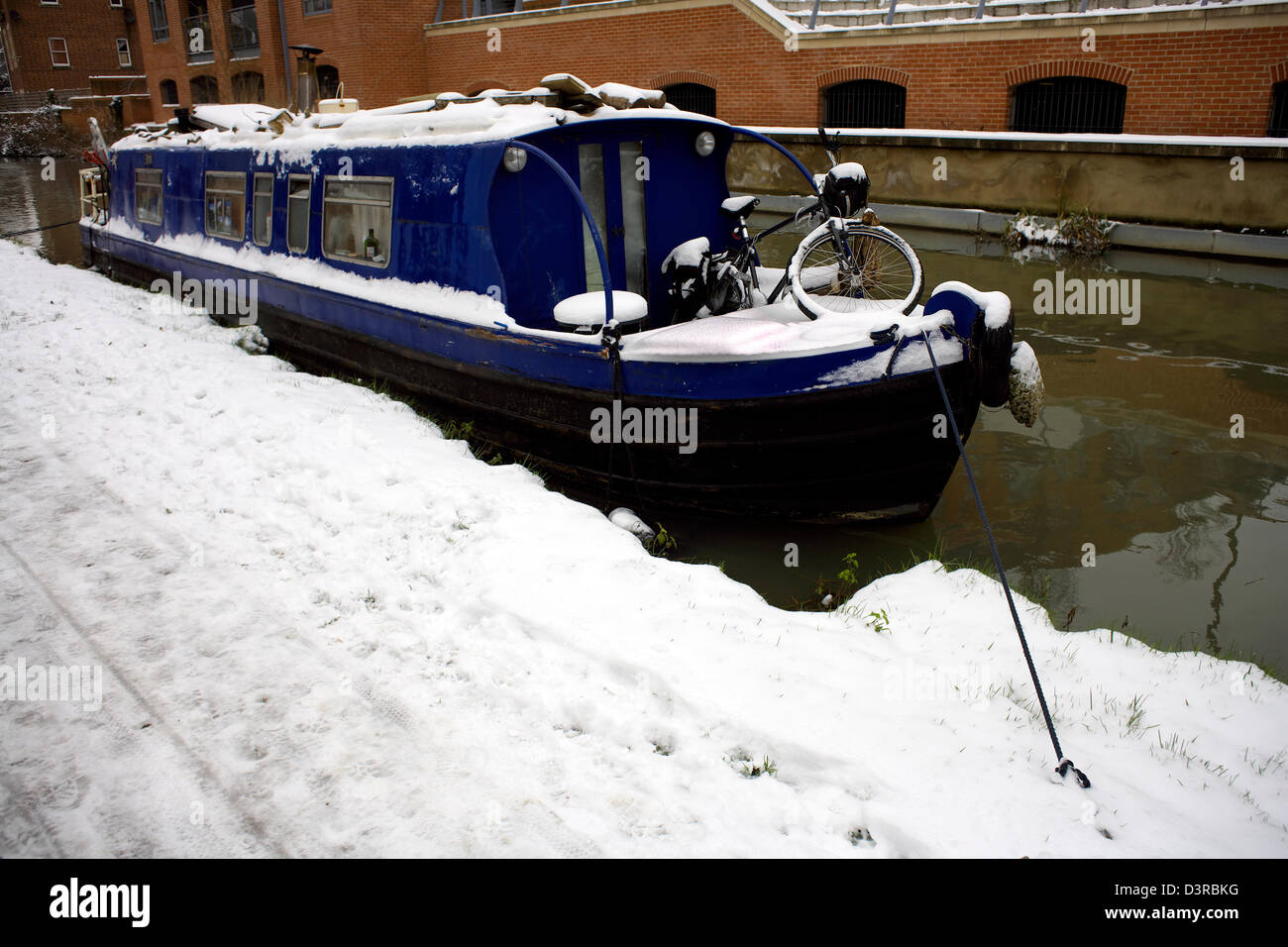 Snow narrowboat and bicycle winter on the South Oxford Canal City of Oxford Oxfordshire Oxon England boat narrowboat - Stock Image