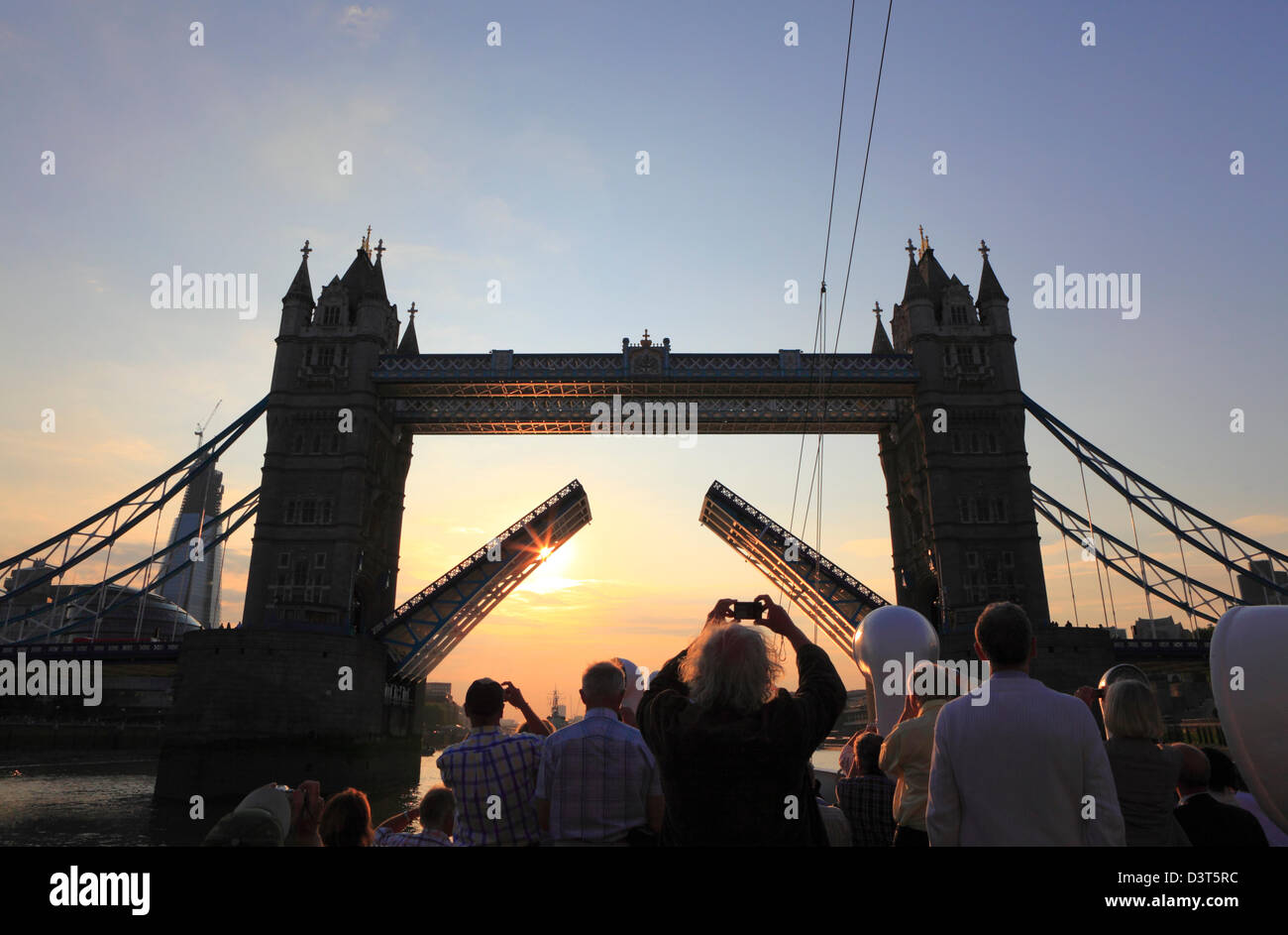 Tourists photographing Tower Bridge at sunset from a boat on the River Thames London England UK GB Taking a photo Stock Photo