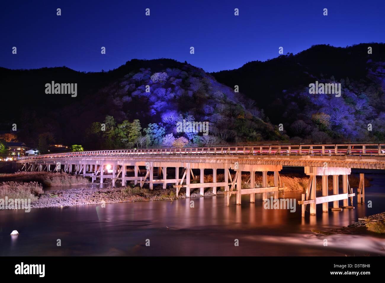 The historic Togetsukyo Bridge, illuminated at night in the Arashiyama district of Kyoto, Japan. - Stock Image
