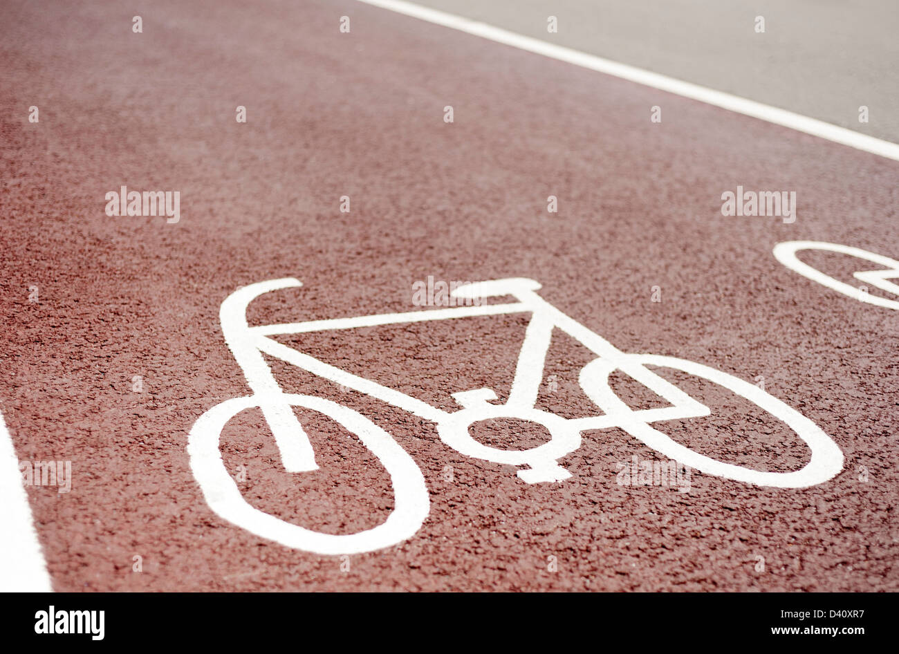 Designated cycle lane path symbol painted on a red asphalt road surface, UK - Stock Image