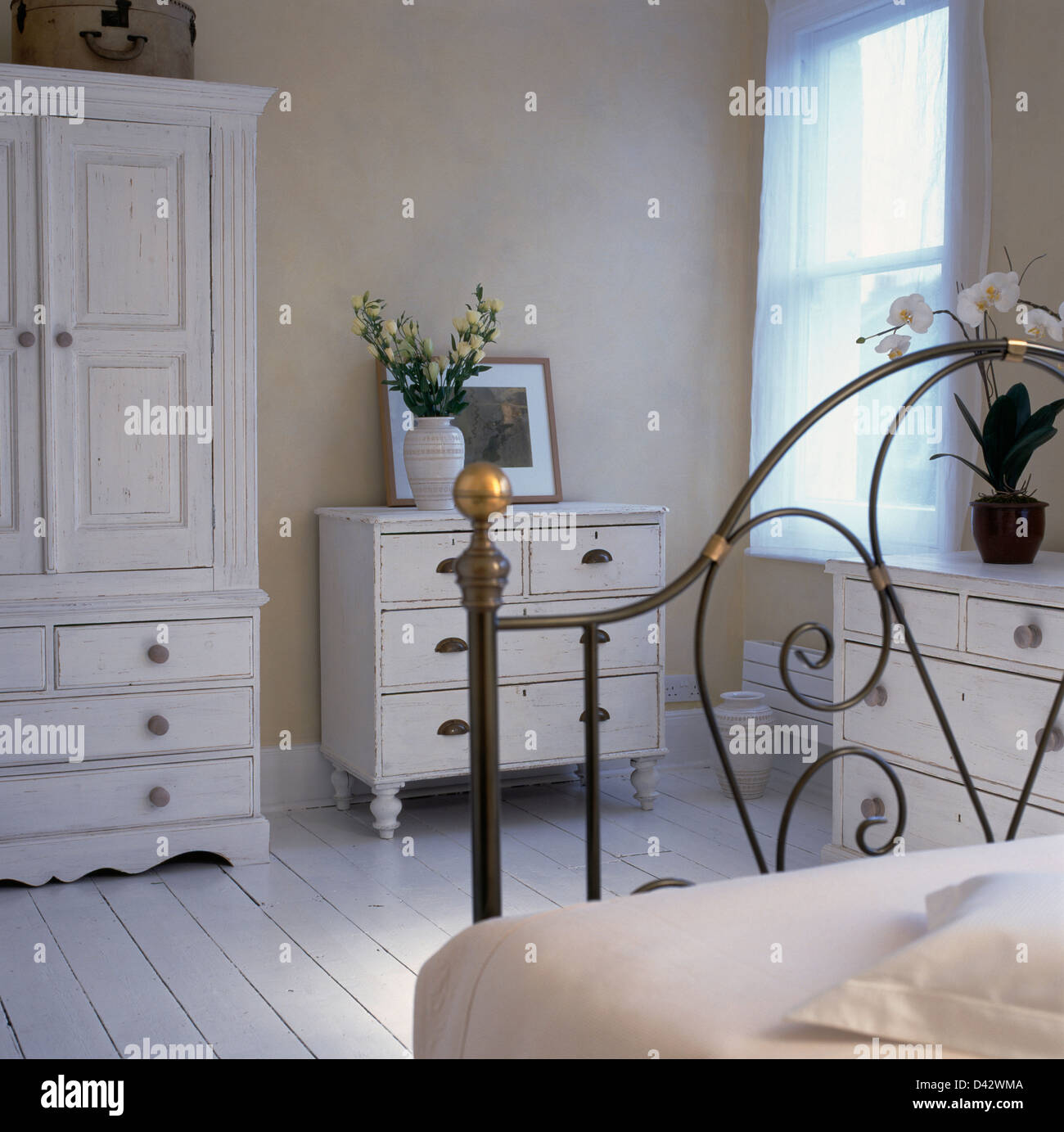 White painted wardrobe and chest-of-drawers in pale beige bedroom ...