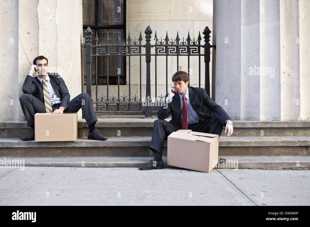 Two wall street men made redundant, carrying boxes of personal effects from work. - Stock Image