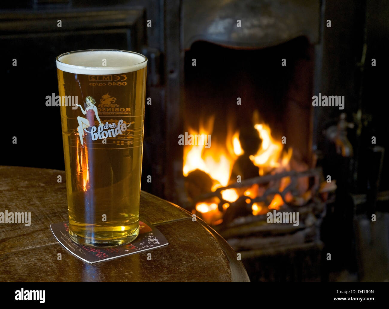 a-pint-of-dizzy-blonde-beer-on-a-pub-table-with-open-fire-in-the-background-D47R0N.jpg