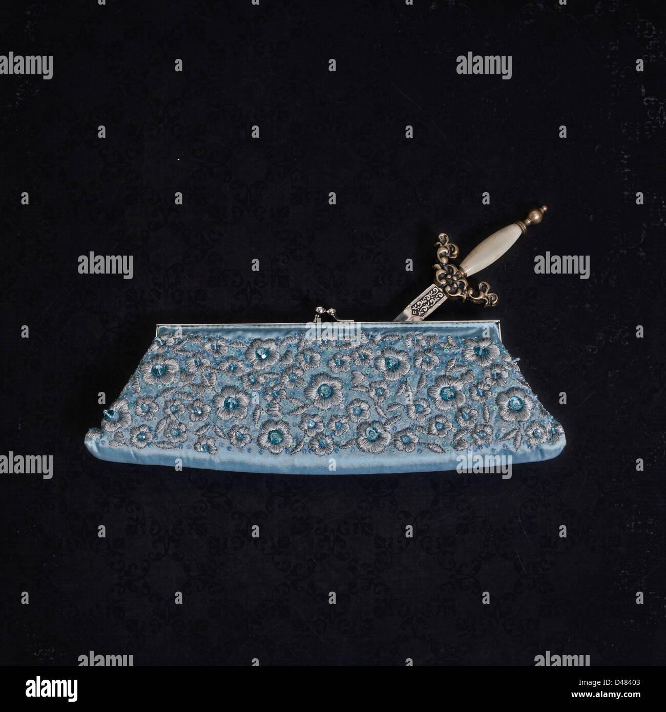 a dagger in an elegant handbag - Stock Image