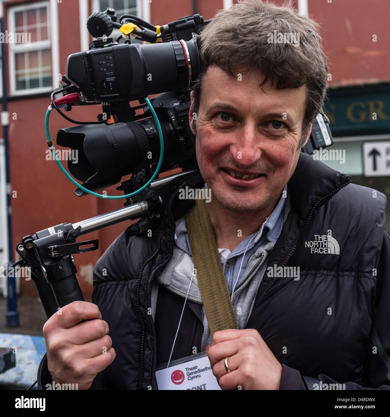 A professional videographer using a Nikon D800 dslr video camera in a shoulder rig, UK - Stock Image