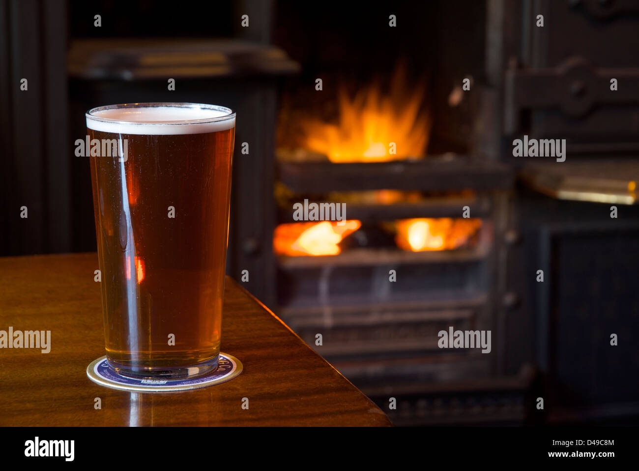 a-pint-of-bitter-on-a-pub-table-with-open-fire-in-the-background-D49C8M.jpg
