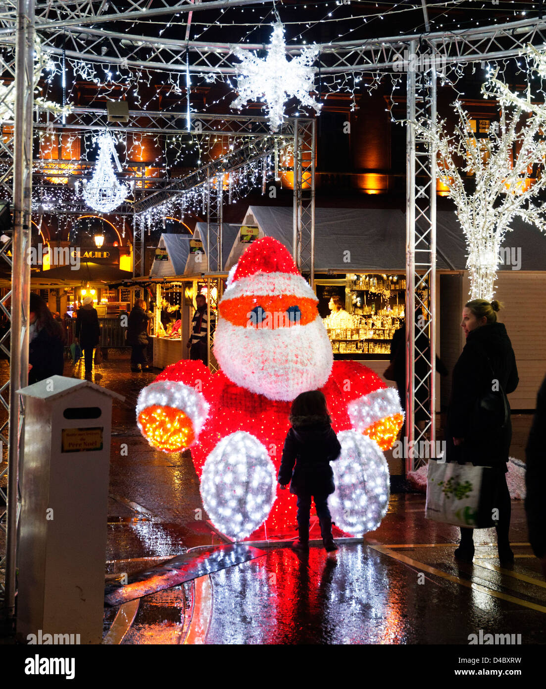 a-little-girl-looking-at-a-large-illuminated-father-christmas-at-the-D4BXRW.jpg