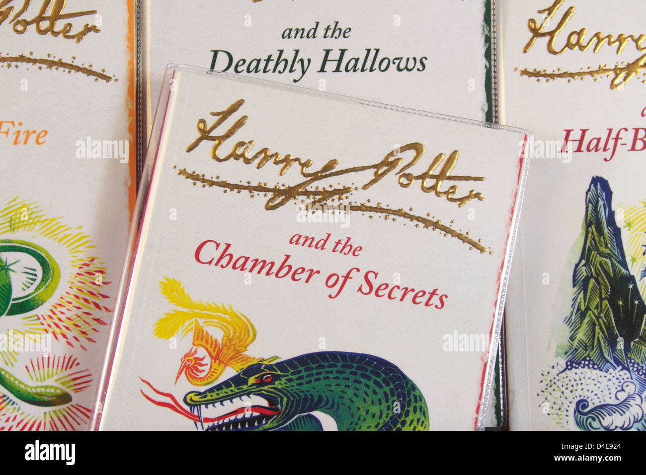 The book cover of 'Harry Potter and the Chamber of Secrets' by JK Rowling sitting on other books in the - Stock Image