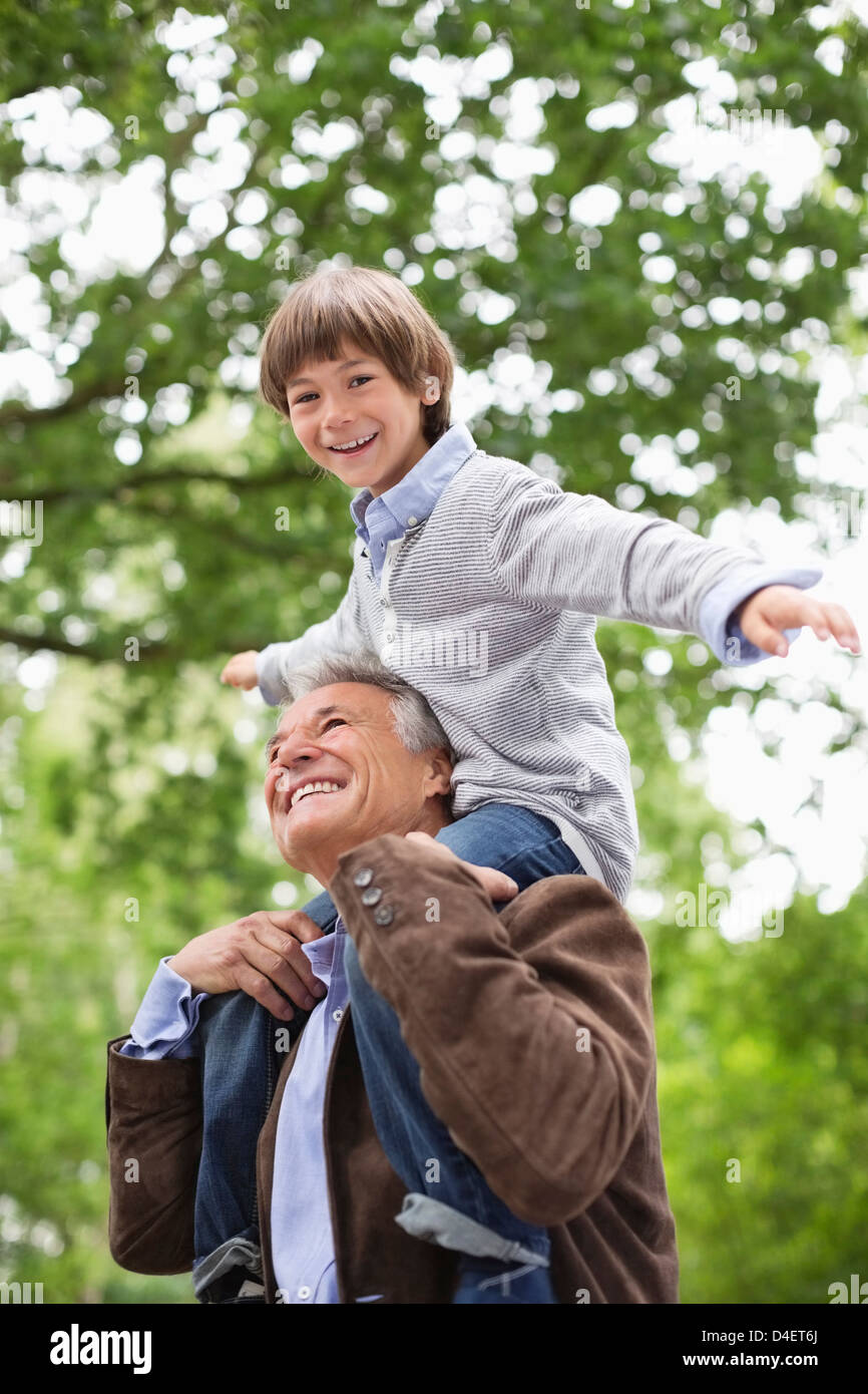 Man carrying grandson on shoulders outdoors - Stock Image