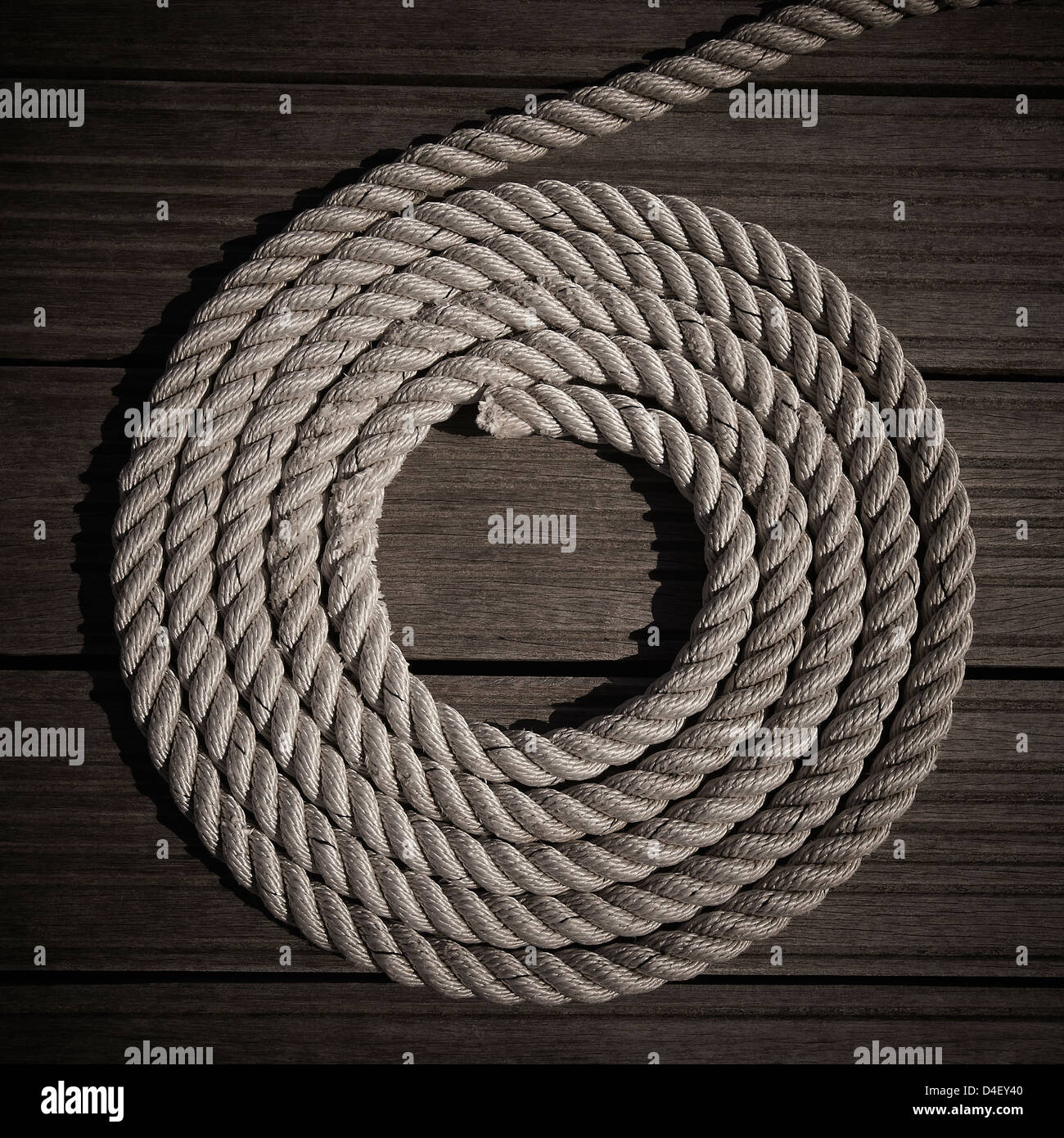 Rope coiled into circle on boardwalk - Stock Image