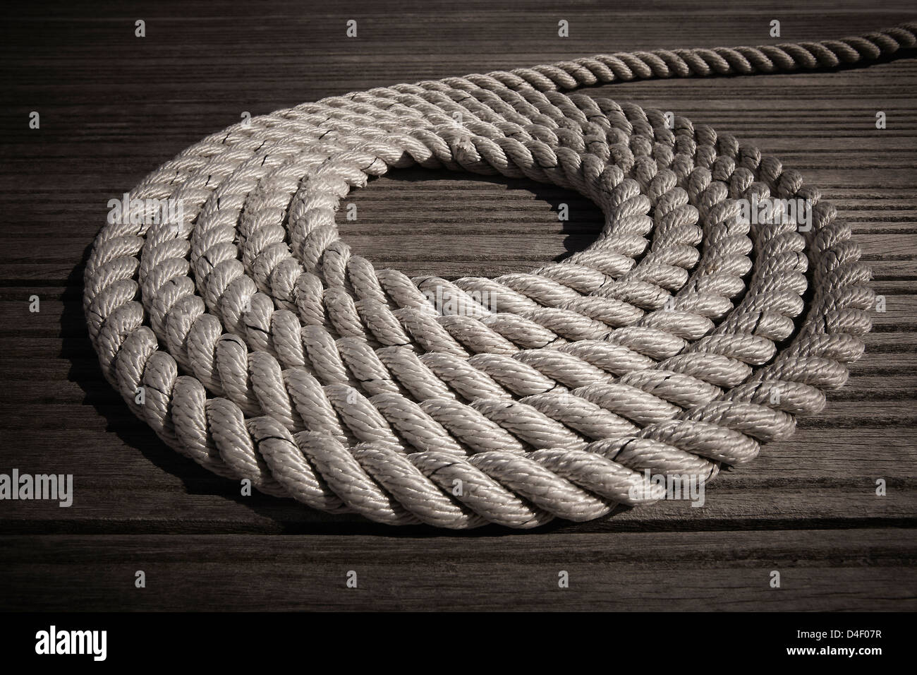 Rope coiled in circle on boardwalk - Stock Image