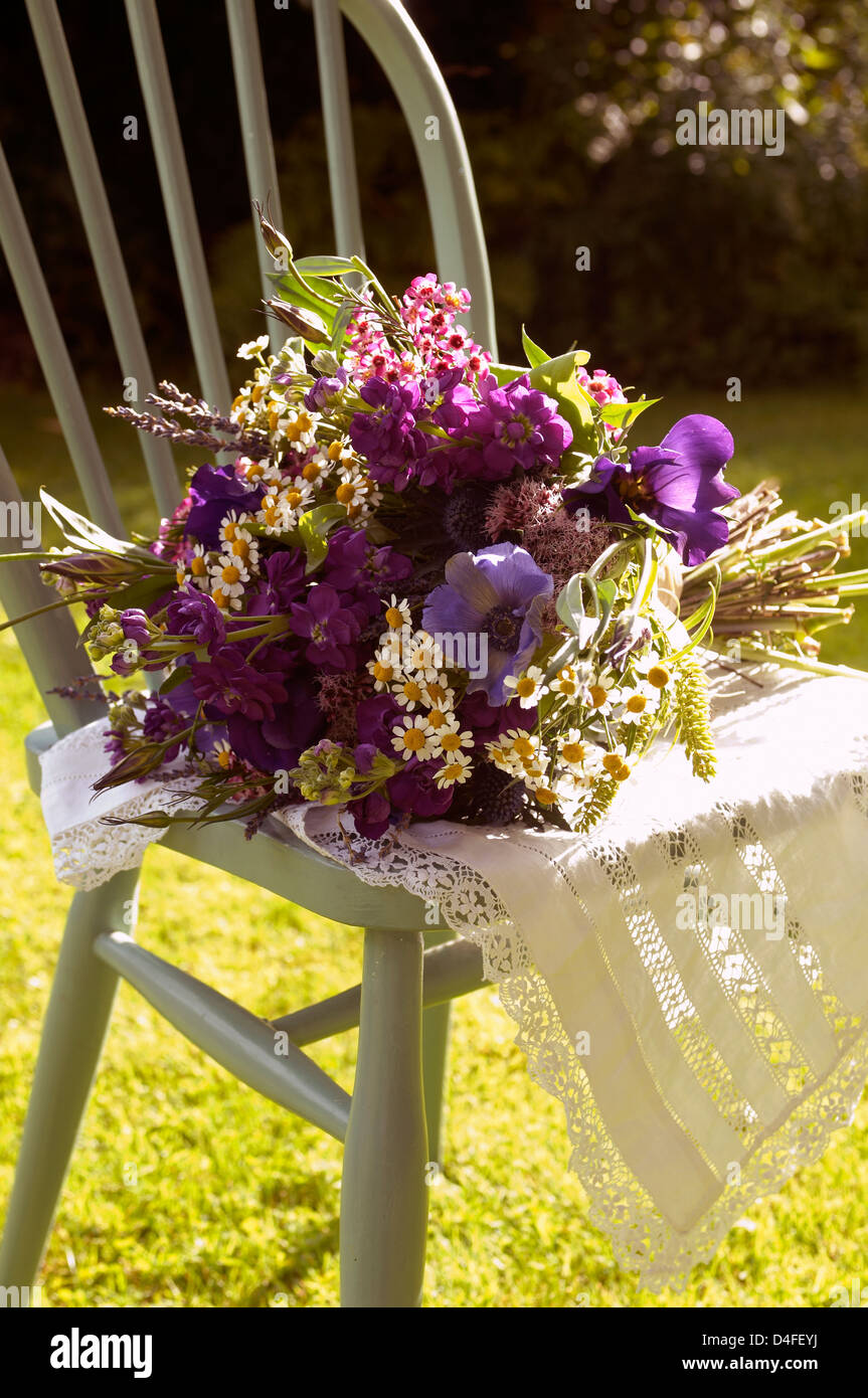 Bouquet of flowers in chair outdoors - Stock Image