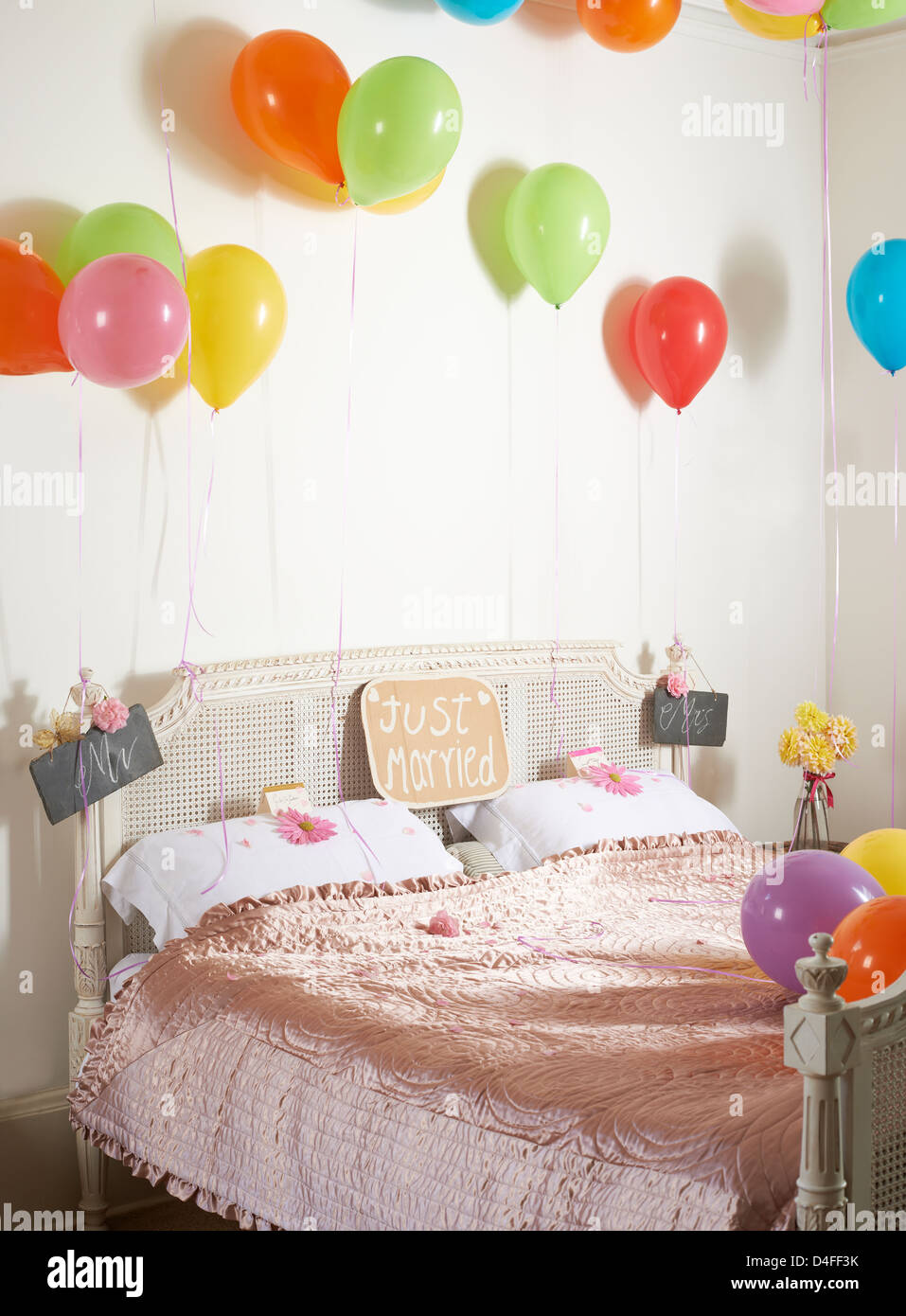 Colorful balloons over marriage bed - Stock Image