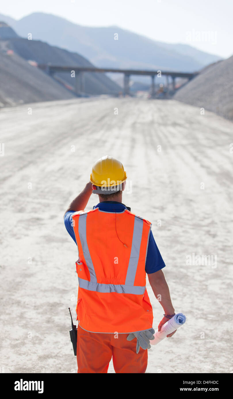 Worker standing on road in quarry - Stock Image